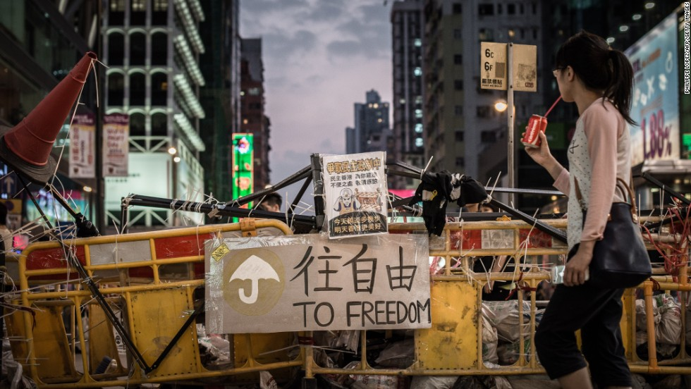 A woman drinks a soda as she walks past a barricade erected by pro-democracy demonstrators in Hong Kong on October 9.