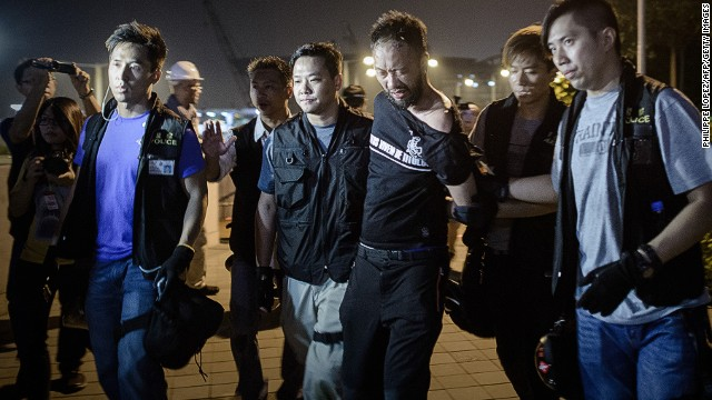 Civic Party member Ken Tsang, one of Hong Kong's pro-democracy political groups, is taken away by policemen, before being allegedly beaten up by police forces as seen on local TV footage shot outside the central government offices in Hong Kong on early October 15, 2014. Hong Kong police vowed on October 14 to tear down more street barricades manned by pro-democracy protesters, hours after hundreds of officers armed with chainsaws and boltcutters partially cleared two major roads occupied for a fortnight. AFP PHOTO / Philippe Lopez (Photo credit should read PHILIPPE LOPEZ/AFP/Getty Images)
