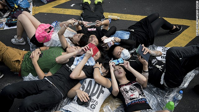 People look at their mobile phones as they lay on the ground at a pro-democracy demonstration occupying Nathan Road, a major route through the heart of the Kowloon district of Hong Kong, on September 29, 2014. Police fired tear gas as tens of thousands of pro-democracy demonstrators brought parts of central Hong Kong to a standstill on September 28, in a dramatic escalation of protests that have gripped the semi-autonomous Chinese city for days. AFP PHOTO / ALEX OGLE (Photo credit should read Alex Ogle/AFP/Getty Images)