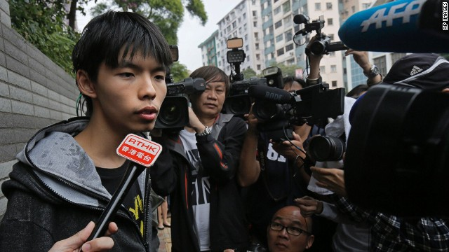 Hong Kong student protest leader Joshua Wong talks to reporters after being hit by eggs outside a court in Hong Kong November 27, 2014.