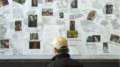 A man looks at photos of some of the victims of the  devastating fire in Lac-Mégantic as part of commemorative events marking the first anniversary in 2014 in Lac-Mégantic, Que.