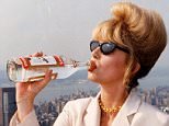 """PKT6067-447162 Television Programme """"ABSOLUTELY FABULOUS"""" 1994 Joanna Lumley filming Absolutely Fabulous in New York.   Patsy,  played by Joanna Lumley,  drinks from a bottle of vodka,  cigarette in hand."""