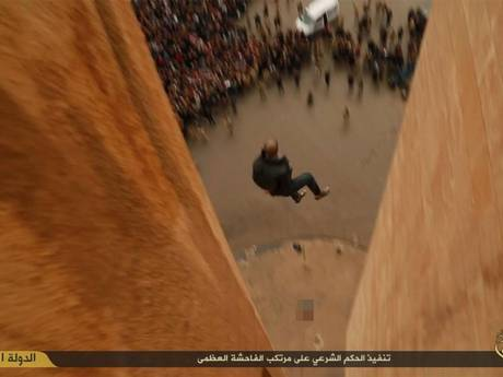 The images appear to show the men being pushed off, as a large crowd controlled by militants watches on from below