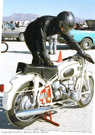 Foreground: rider dressed in black leathers kick starting bmw motorcycle.