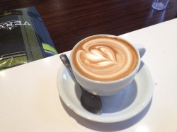 The Caffé Medici cappuccino: wet, no foam, with bags of Verve Sermon in the background