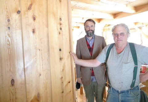 Josiah (right) and Steve Ahlgren stand next to a wall made of hemlock wood taken from an old barn. Steve re-sawed the wood, planed, sanded and used it to cover a wall in his home. According to Steve, the hemlock is easily 300 years old.