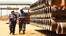 Technicians walking through pipe storage area at BP's operations support base in Luanda, Angola.
