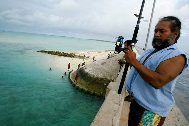 """<span class='image-component__caption' itemprop=""""caption"""">In this March 30, 2004 file photo, a man fishes on a bridge on Tarawa atoll, Kiribati. Fearing that climate change could wipe out their entire Pacific archipelago, the leaders of Kiribati are considering an unusual backup plan: moving the populace to Fiji.</span>"""