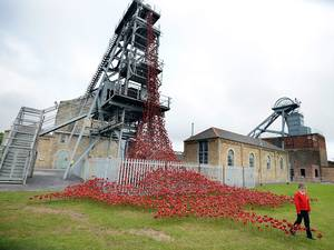 11 September 2015: Neve Stuart, 9, of Ashington views the 'Weeping Window' part of the sculpture of poppies from the Tower of London on display at Woodhorn Museum in Ashington, Northumberland. The poppies are on a UK tour and can be seen at two other locations at the Yorkshire Sculpture Park and St George's Hall in Liverpool as well as this once until 1 November 2015