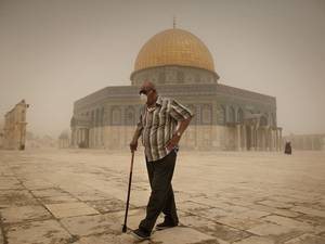 A Palestinian man wears a mask to protect his face from the dust as he walks past the Dome of the Rock mosque in the al-Aqsa Mosque compound, during a sandstorm, in the old city of Jerusalem