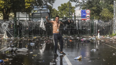A man reacts after Hungarian riot police use water cannon to push back refugees at the Hungary-Serbia border near the Serbian town of Horgos on September 16.