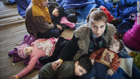 A Syrian refugee mother comforts her children, after being rescued from a fishing boat carrying 219 people who had hoped to reach Europe. They are among millions uprooted by war.