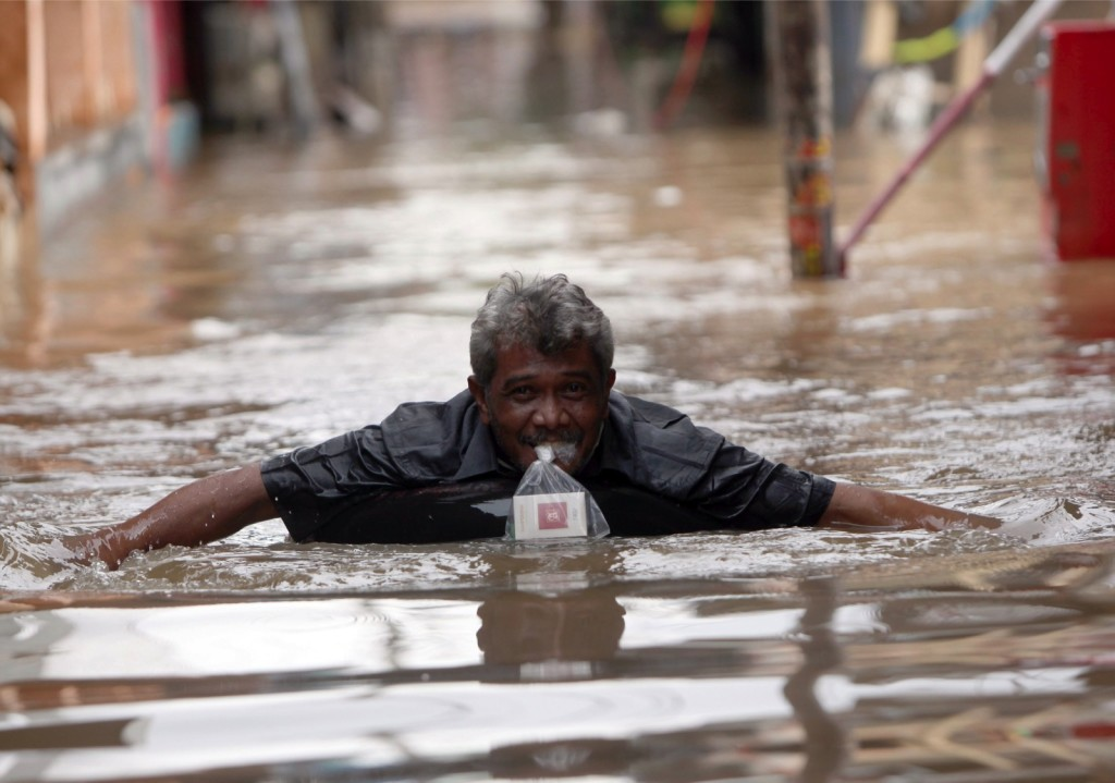 A man wades through a street affected by flood waters in Jakarta, Indonesia, on Jan. 20, 2014. (EPA Photo/Adi Weda)