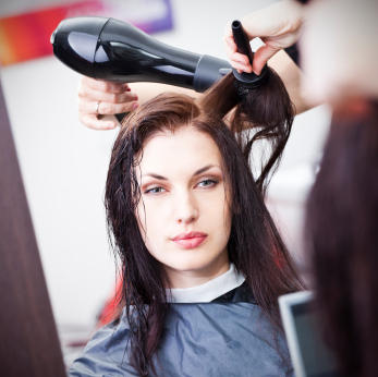 Hairdresser drying woman's hair with hair dryer