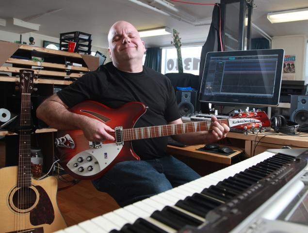Cremer practices on his Rickenbacker guitar at his computer repair shop in Reading.