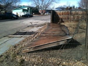 High winds blew over this fence when the force broke the dry rotted posts.