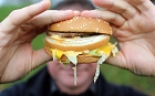 A man holds a burger from a fast food outlet