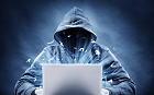 Cybercrime image of hooded person and laptop