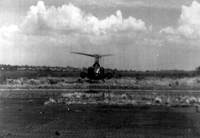 PICTURE - UH-1B HELICOPTER WITH TOW MISSILES lifts off strip at Pleiku.