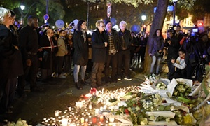 Lead singer Bono, The Edge, Larry Mullen Jr and Adam Clayton pay homage to victims near the Bataclan concert hall in Paris.