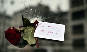"""A red rose, with a sign that reads, """"In the name of what?"""" was placed in a bullet hole in the window of a Japanese restaurant next to 'La Belle Equipe' on Rue de Charonne."""