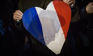 A heart shaped sign with the colors of the French flag is held as people hold a vigil for victims of the Paris terrorist attacks in Trafalgar Square.