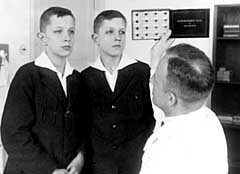 American eugenicist Dr. Otmar Freiherr von Verschuer examines twins. His assistant, Josef Mengele, would continue these experiments at Auschwitz.