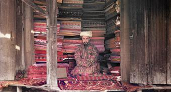 A cloth merchant sits in his stall in Samarkand (present-day Uzbekistan)