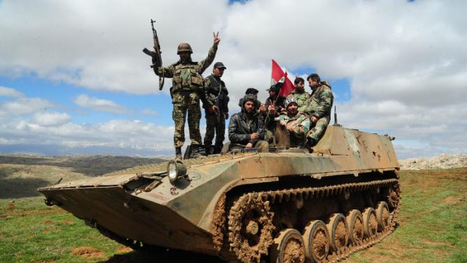 A handout picture released by the Syrian Arab News Agency (SANA) on March 31, 2015 shows pro-government fighters sitting on an armoured vehicle in the mountains surrounding the city of Zabadani