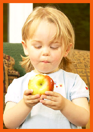 Healthy snacks for kids are moreimportant than you think: Little girl toddler eating an apple.