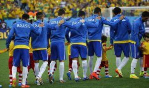 Brazilian football team walks onto the pitch with hands on shoulders