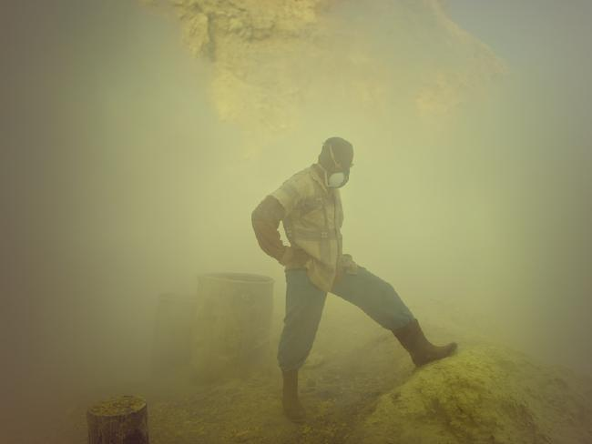 A worker pauses near the acid lake and is waiting for a clearer view and breath. Many workers have respiratory problems and have to cough even days after they left the volcano.