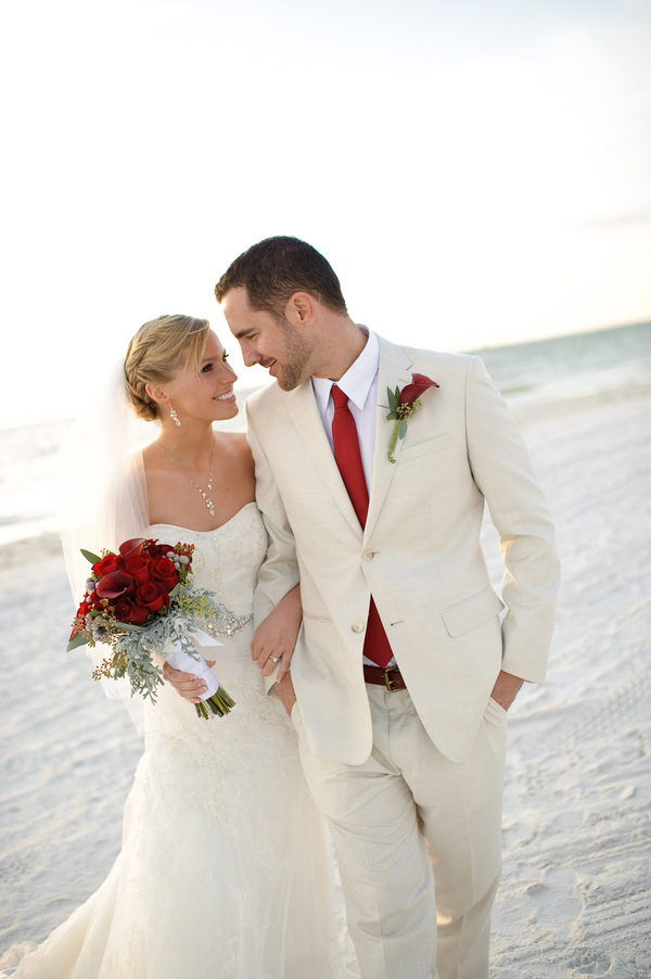 bride and groom walking on the beach, strapless lace Casablanca wedding dress, classic men's attire, red silk tie, red calla lily boutonniere, red rose and calla lily bouquet, romantic Christmas beach wedding, Luminaire Foto