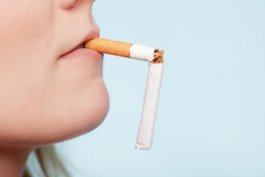 Bouche de femme de profil tenant une cigarette cassé dans sa bouche pour symboliser la possible interdiction de la vente de tabac pour les jeunes nés après l'an 2000