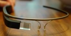 The Google Glass Explorer. There are no lenses. A small computer display is on the top right corner of the frame.