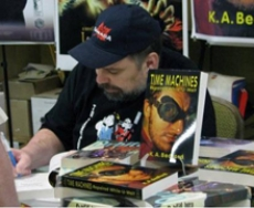 Australian author K.A. Bedford signing a copy of his book Time Machines on a table surrounded by many copies of the book. He has a beard and is wearing a black cap and black tshirt.