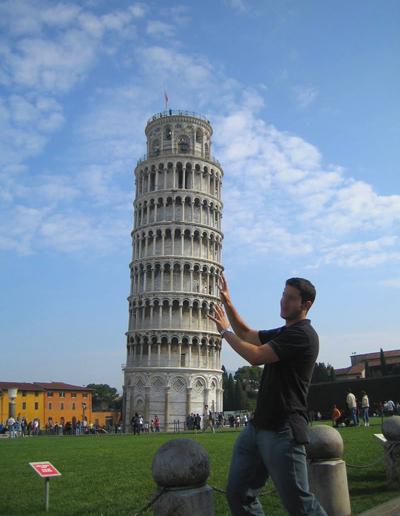 صورة لسائح يبدو فيها وكأنه يحاول أن يحمي برج بيزا المائل من السقوط