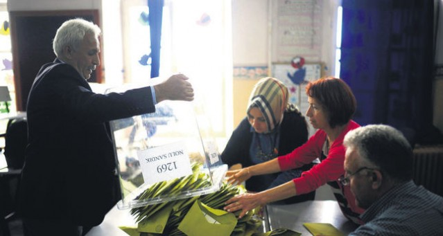 An election official empties a ballot box at a polling station during the parliamentary election in Istanbul