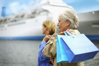 Two woman with shopping bags stand at a port in front of a cruise ship.