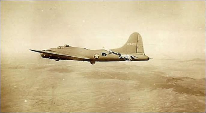 """Stricken B-17 """"All American"""" miraculously flying after collision with a German fighter, photographed by the crew of another bomber in her formation."""