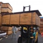 FORK LIFT REMOVING THE DAMAGED CRATE FROM THE STACK FOR OUR INSPECTION damaged cargo surveying