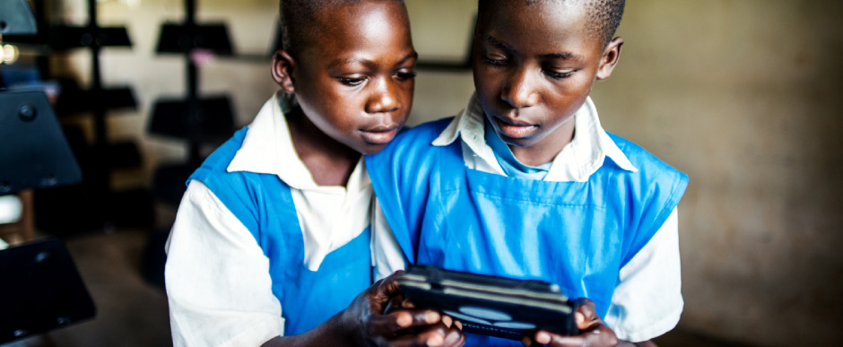 Girls in Ghana browse books on their e-reader