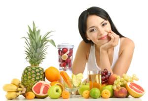 Eine Frau macht sich eigenen Obstsaft mit einem Entsafter