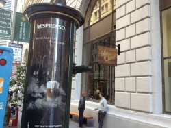 Coffee Cultures' front window getting muscled in by the America's Cup and dreck Nespresso marketing