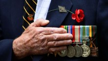 An ex-serviceman holds his hand over his heart during the Anzac Day march in Sydney.