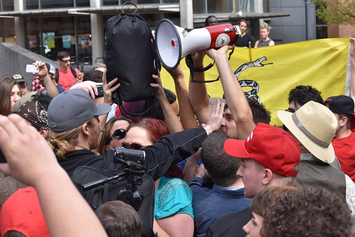An Infowars guy puts his hand in the face of an anti-Trump guy, who used the siren from his megaphone for most of the rally