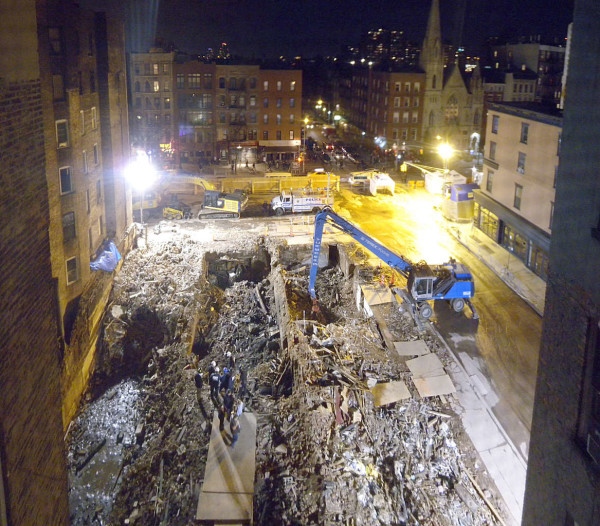 A photo taken by a Community Emergency Response Team (CERT) volunteer from the  E. Seventh St. building just west of the explosion site, showing the three craters left where the tenements had stood.