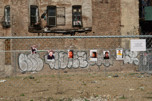 Photos of the disaster's two victims hang on the fence around the barren site. Photo by Tina Benitez-Eves
