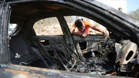 Illustrative: A Palestinian boy looks at a car belonging to Palestinians, which residents said was burnt by Jewish settlers, in a village near the West Bank city of Ramallah on October 2, 2015. (Flash90)