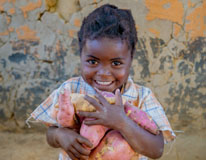 Deli, 3, holds the sweet potatoes that her mother, Monica has grown with the help of Concern's RAIN programme in Zambia. Photo taken by Gareth Bentley/Concern Worldwide.
